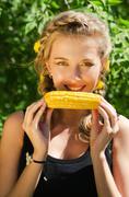 Woman eating corn-cob Stock Photos