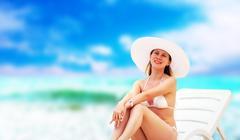 Stock Photo of Young beautiful women on the sunny tropical beach in white bikin