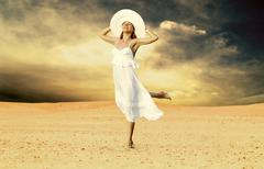 Stock Photo of Young beautiful women in white, relaxation at sunny desert
