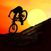 Stock Photo of Silhouette of a man on muontain-bike, sunset