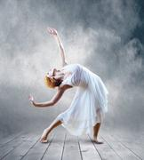 Stock Photo of Woman dancer seating posing on background