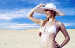 Stock Photo of Young beautiful women in whitebikini and hat, relaxation at sunn