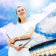 Stock Photo of Young happy women or student with laptop on the business backgro