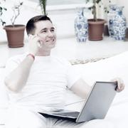 Smiling young man working on laptop computer and call by phone a - stock photo