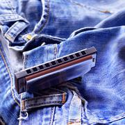 Harmonica on the jeans - stock photo