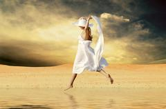 Young beautiful women in white, jump on the water at sunny deser - stock photo