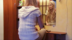 Beautiful young girl applying cosmetic in front of mirror Stock Footage