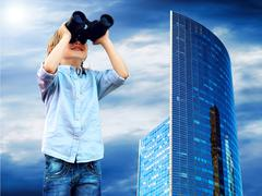 Young boy watch in the field-glass, outdoors. - stock photo