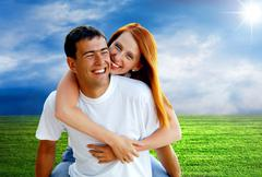 Stock Photo of Young love couple smiling under blue sky