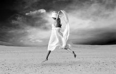 Young beautiful women in white, relaxation at sunny desert Stock Photos