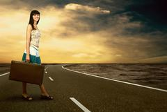 Stock Photo of Young woman waiting on the road with her vintage baggage