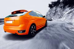 Stock Photo of orange car going fast