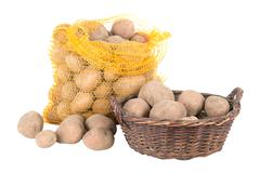 Potatoes in a bag and a basket Stock Photos