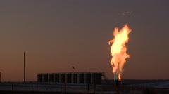 Fracking gas flare burns at dusk Stock Footage