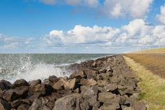 Waves near a Dutch breakwater with Windturbines - stock photo