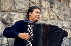 Male playing on the accordion against a grunge background Stock Photos