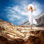 Stock Photo of Beautiful girl in White on the mauntain under sky with clouds