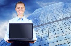 Happiness businesswoman with laptop on blur business architectur - stock photo