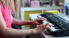 Cute little school girl playing an electric piano Stock Footage