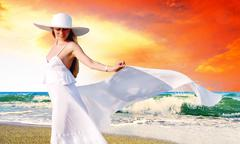 Stock Photo of Young beautiful women in the white with pareo on the sunny tropi