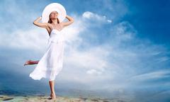 Young beautiful women in the white with pareo on the blue sky ba Stock Photos