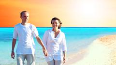 Stock Photo of View of happy young couple walking on the beach, holding hands.