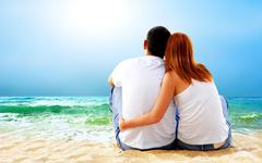 Stock Photo of Sea view of a couple sitting on beach.