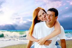 Stock Photo of Young love couple smiling under tropical beach