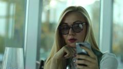 sexy blonde young woman in cafe messaging on smartphone - stock footage