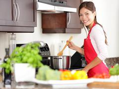 Cooking woman in kitchen making food for dinner Stock Photos
