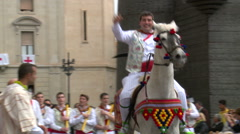Folk group in parade man riding horse and slowly walking farmers Stock Footage