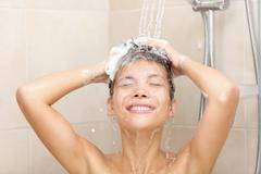 Woman in shower washing hair Stock Photos