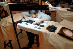 Workers embroider with silk - stock photo