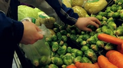 Man selecting brussel sprout in grocery store Stock Footage