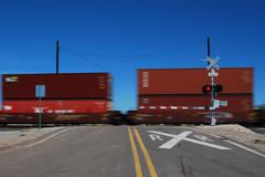 Railroad shipping containers passing through a crossing in the Arizona desert - stock photo