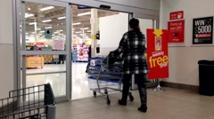 People with Shopping Cart Walking Through the Doors at superstore Stock Footage