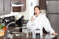 Yawning coffee woman in morning standing by kitchen table - stock photo