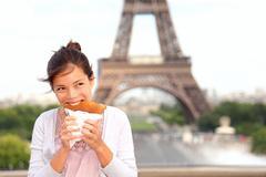Paris woman eating pancake in front of Eiffel Tower - stock photo