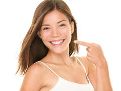 Dental teeth - perfect smile woman pointing at toothy smile looking happy - stock photo