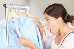 Shopping woman shocked over price tag on expensive clothing in retail store - stock photo