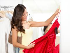 Woman shopping for dress in clothing retail store. - stock photo