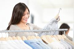 Shopper woman shopping clothes in clothing retail shop during sale. - stock photo