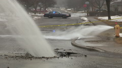 Massive water main break gushing on city street in winter Stock Footage