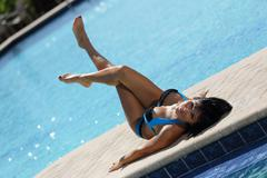 Image of a bikini model sunbathing by the pool Stock Photos