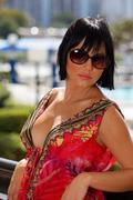 Model in oversized sunglasses glancing over shoulder - stock photo