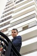 Image of a businessman posing with a highrise building in the background Stock Photos