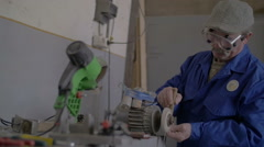 Technician sharpening a knife with an electric tool with sparks Stock Footage