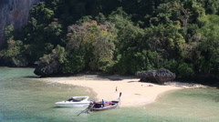 Motor speed boat tied up at rocky island coast Stock Footage
