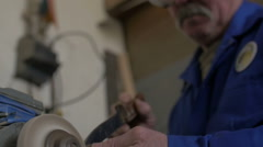 Technician sharpening a knife with an electric tool with sparks - stock footage