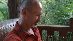 Old man prints text on tablet PC at verandah Stock Footage
